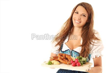 maedchen mit dirndl und bayrischen spezialitaeten