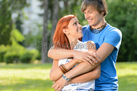teenage couple embracing looking at each