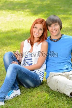 teenage couple sitting on grass embracing