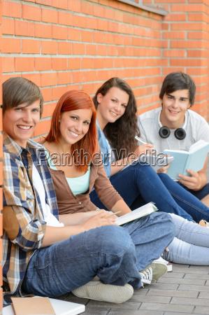 college studenten ausserhalb von mauer sitzen