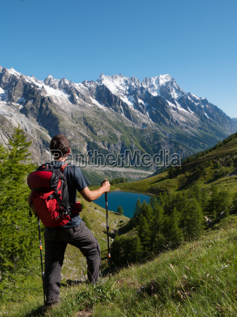 hiker admiring mountain landscape in val