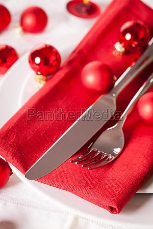 rote serviette mit weihnachtlichen glaskugeln und