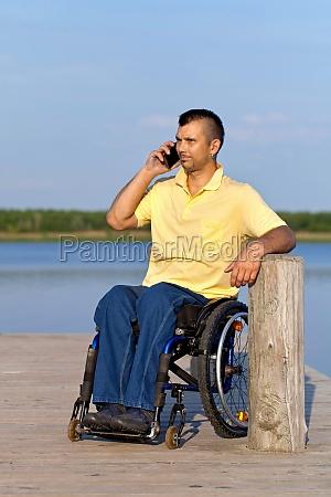 rollstuhlfahrer beim telefonieren mit handy