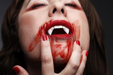 female vampire licking blood