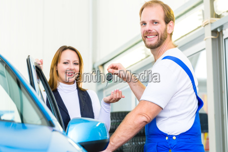 customer and mechanic at car in