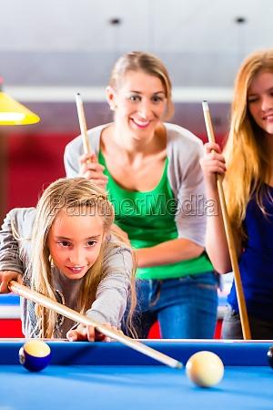 maedchen spielt pool billard mit familie