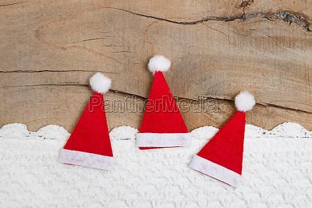 blick auf drei weihnachtsmuetzen mit haekelstreifen