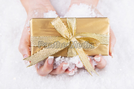 frau haelt einen goldenen weihnachtsgeschenk in