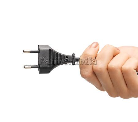 hand haelt schwarzen elektrischen stecker mit