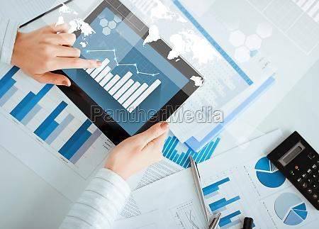 frau mit tablet pc und diagrammpapiere