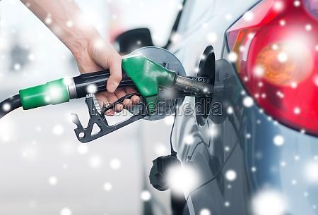 mann pumpt benzin im auto an