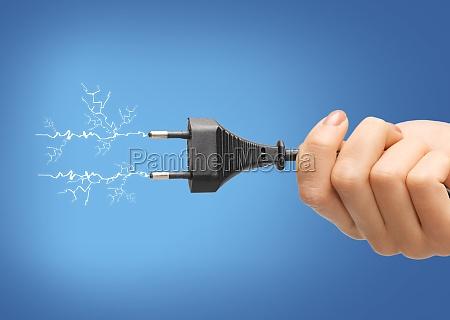 hand haelt schwarze elektrische stecker mit