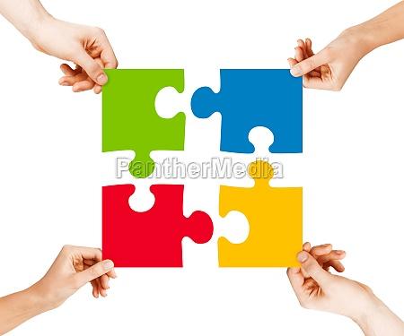vier haende die puzzleteile verbinden