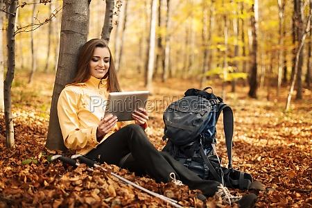 sitting female hiker using digital tablet