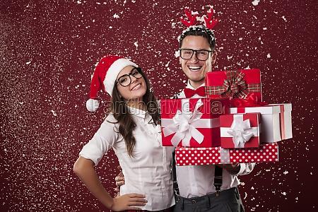 laechelnde nerd paar mit vielen weihnachtsgeschenken