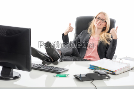 woman at desk showing thumbs up