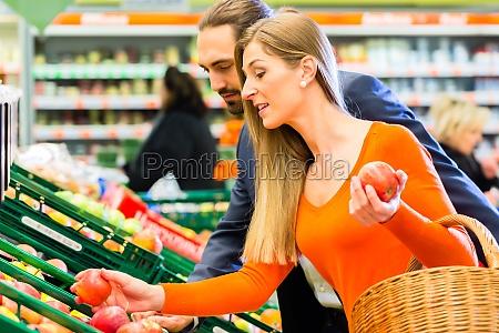 paar waehlt obst im lebensmittelmarkt aus