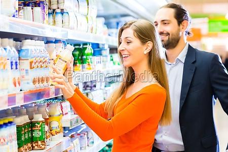 paar mit einkaufswagen im supermarkt