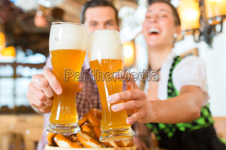 bayrisches paar stoesst mit bier an
