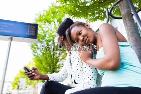 african couple waiting at bus stop