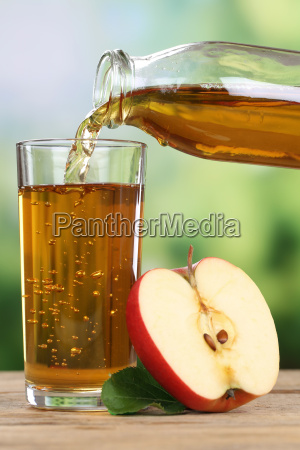pouring apple juice from red apples