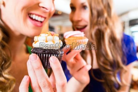 women eating muffins when drinking coffee