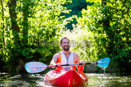 man is riding in kayak on