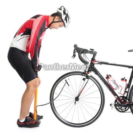 asian cyclist using air pump