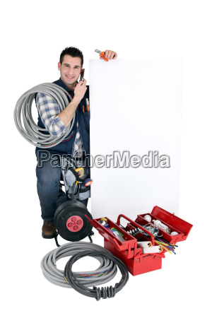 tradesman posing with a blank sign