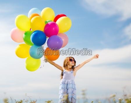 froehliches maedchen mit bunten luftballons