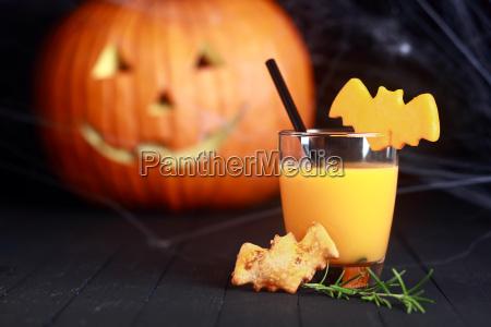 ein glas orangensaft dekoriert fuer halloween