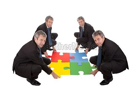 senior business people assembling a jigsaw
