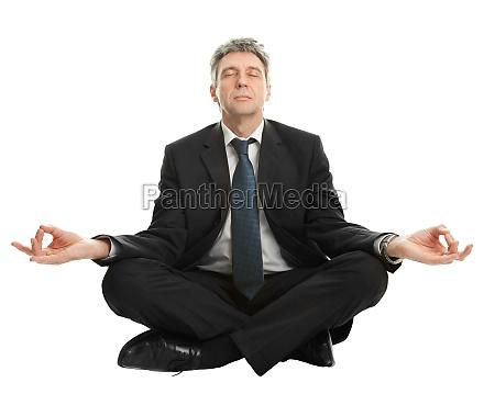 geschaeftsmann der in yogaposition sitzt