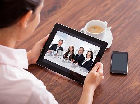 frau video conferencing on digital table