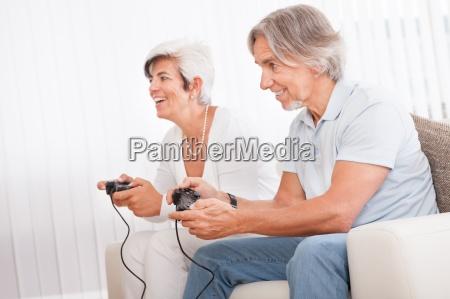 middle aged couple playing computer games