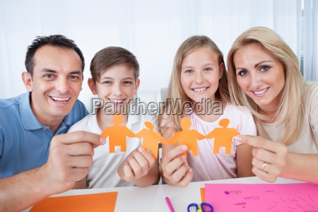 family holding paper people in hand