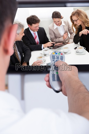 man changing television channel through remote