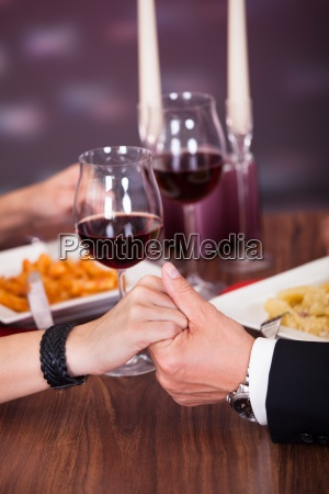 couple holding hand at restaurant