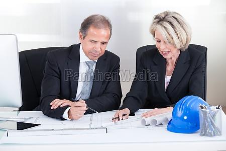 zwei architekten blick auf plaene