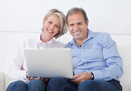 glueckliches paar arbeitet auf laptop