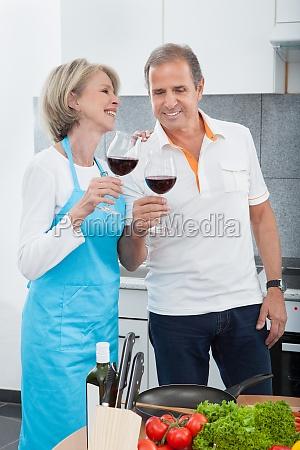 happy mature drinking wine in kitchen