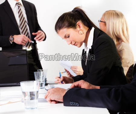 businesswomen taking notes at the presentation