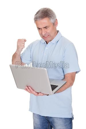 successful businessman holding laptop