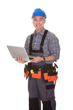 technician holding laptop