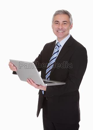 happy mature businessman using laptop