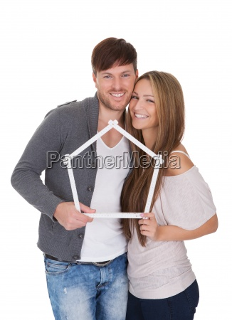 smiling couple posing inside a frame
