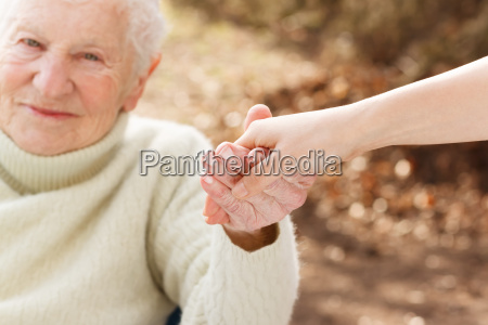 senior woman holding hands with young