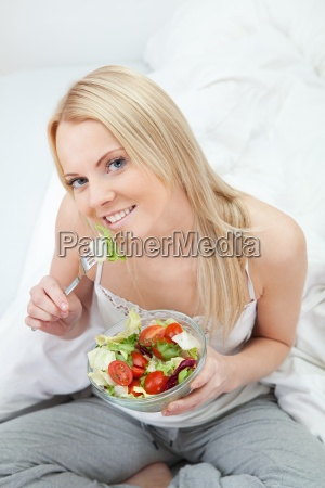 beautiful woman eating green salad