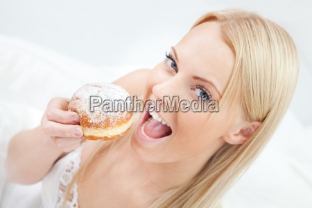 schoene frau isst leckeren donut