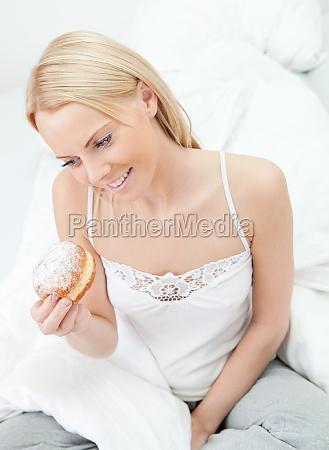 beautiful woman eating tasty donut